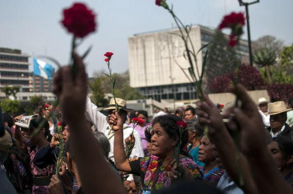 Ixil indigenous women hold up flowers in protest outside court in Guatemala City on Friday (photo by Luis Soto/AP).